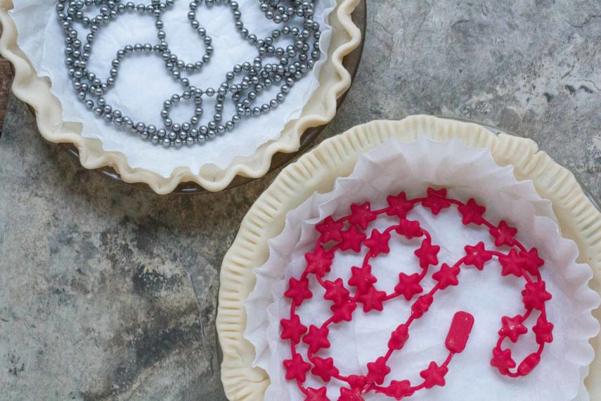 pie weights in two pie crusts. One is a metal chain and one is a silicone chain.