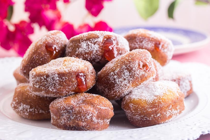 pile of gluten-free jelly doughnuts on white plate; jelly oozing out