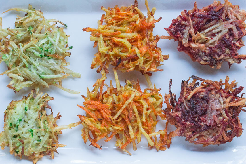 three kinds of vegetable latkes: zucchini, carrot and beet on a white plate