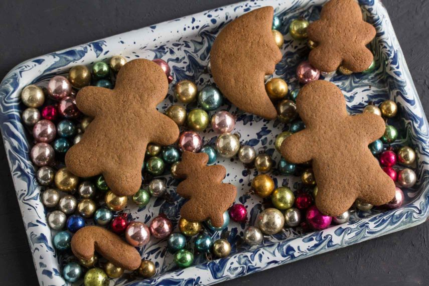 undecorated gingerbread cookies on a blue and white enamel tray with antique Christmas tree ornaments
