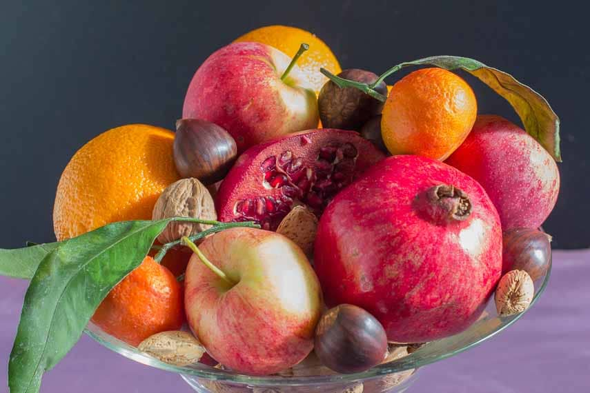 Low FODMAP fruits and nuts along with apples in a clear glass compote dish. Tips for Hosting a party