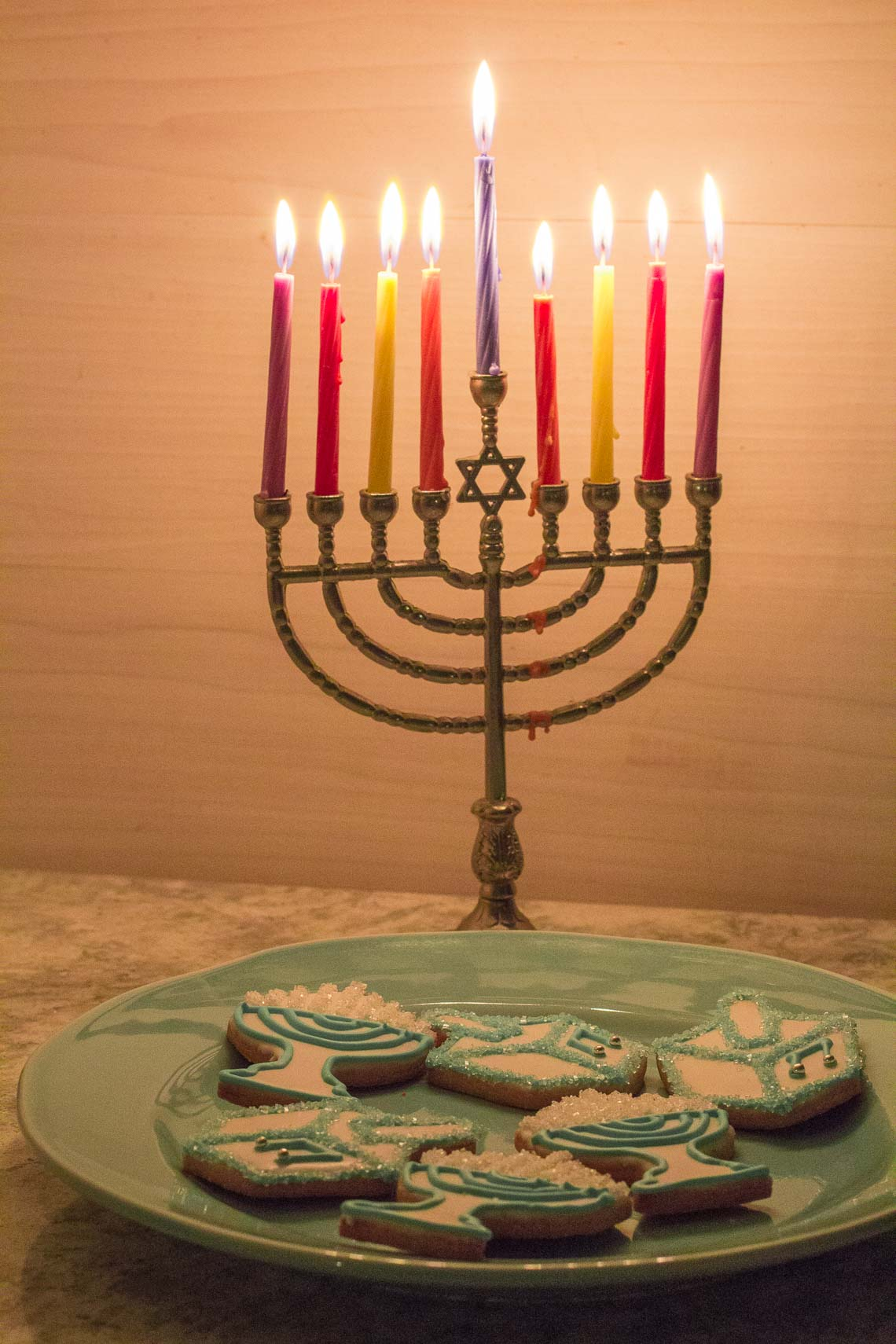 Hanukkah cookies on a plate with Menorah in background