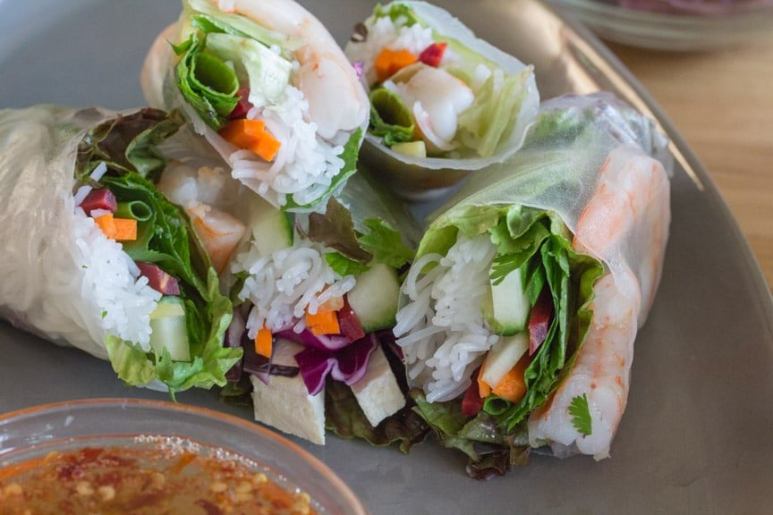 Summer Rolls cut open on a plate with a bowl of dipping sauce.
