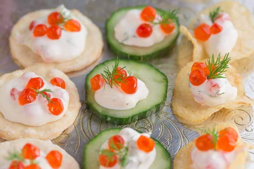 Lactose-free low FODMAP caviar dip closeup on potato chips, rice crackers and cucumbers