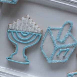 closeup of blue and white Hanukkah cookies on a white plate