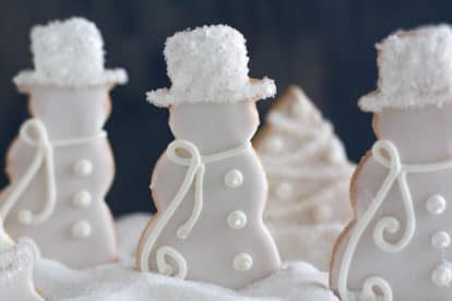closeup of decorated sugar cookies in a white Christmas theme in a snow bank of sugar