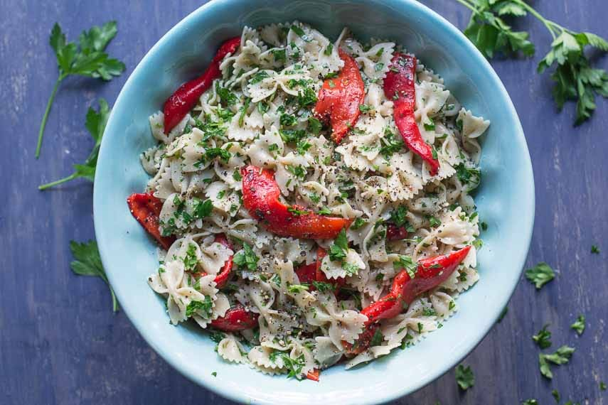 farfalle with roasted red peppers and parsley in a blue bowl overhead shot