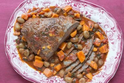 overhead image of brisket with sweet potatoes & grapes in a red and white platter