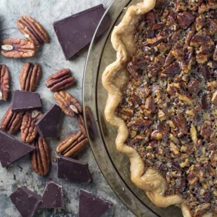overhead image of chocolate pecan pie with whiskey with fluted crust