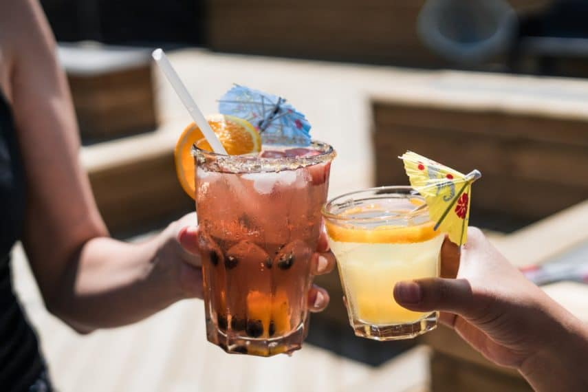 A cheers between two iced drinks with umbrellas