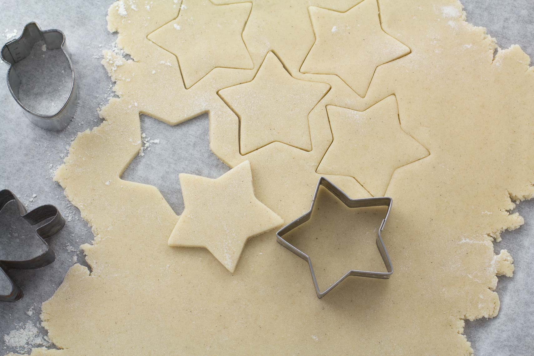 raw rolled sugar cookie dough rolled out with star cookie cutter