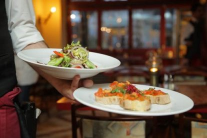 Waiter serving two white plates of food, one with vegetables and one with bruschetta