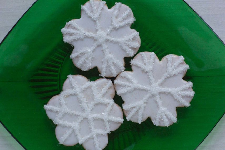 snowflake decorated sugar cookies on a green glass plate