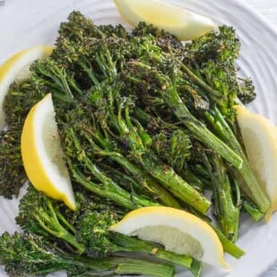 spicy roasted broccolini with garlic and lemon on a round white plate and a white wood background