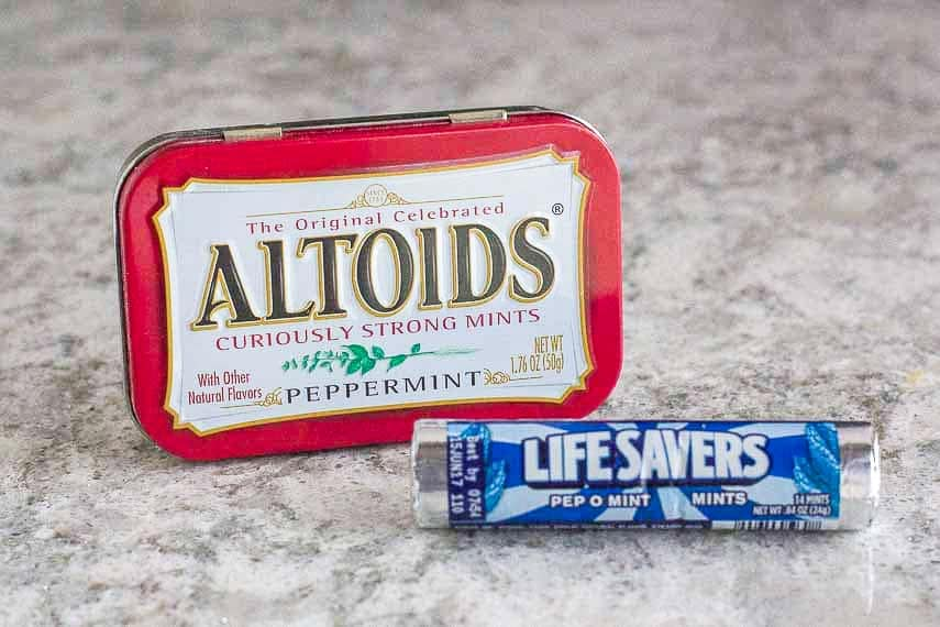 Breath mints on grey quartz counter in their packaging- Altoids and LifeSavers
