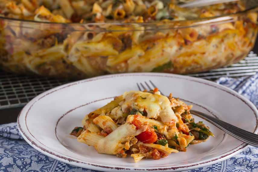 baked ziti on plate with casserole in background