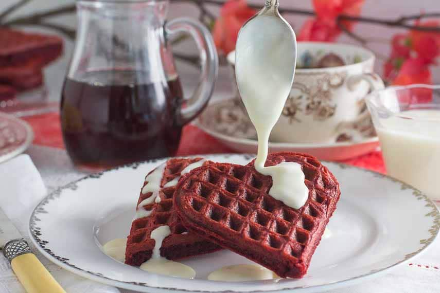 Gluten Free Low FODMAP red velvet waffles with lactose free cream cheese drizzle being poured on top