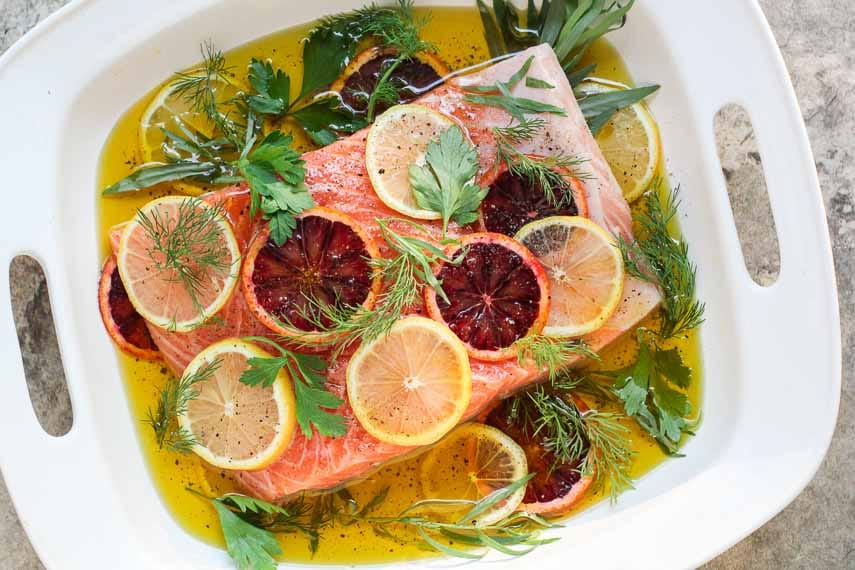 Oil Poached Salmon with fresh herbs and slices of lemon and blood orange