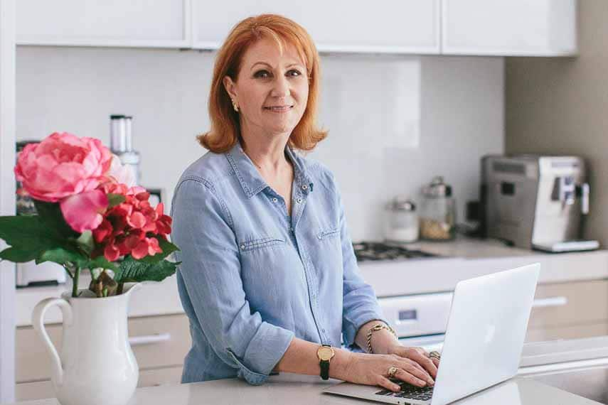 Suzanne Perazzini at her kitchen counter using her laptop