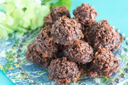 a mound of chocolate macaroons on a plate; aqua background and flowers on the side