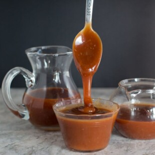 salted caramel sauce pouring from spoon against a black background