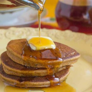 closeup of gingerbread pancakes on a yellow plate, butter melting on top and maple syrup being poured over the stack