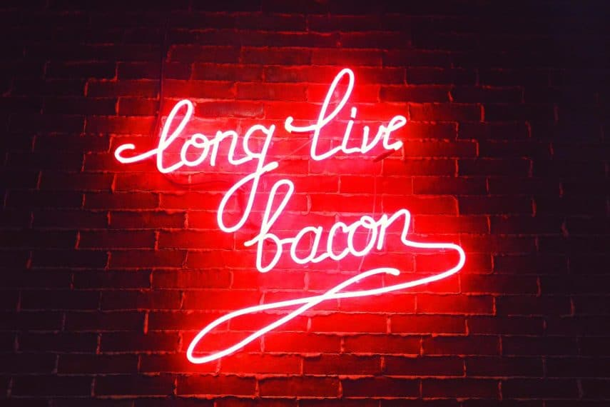 Red neon sign saying Long Live Bacon against a brick wall.