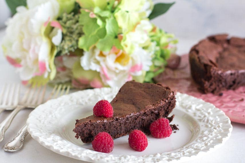 flourless chocolate cake on a white plate with fresh raspberries