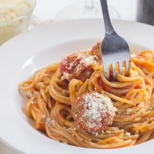 fork twirling in spaghetti & meatballs, in a white bowl