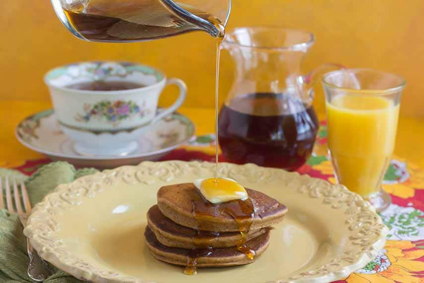 gingerbread pancakes on a yellow plate, butter melting on top and maple syrup being poured over the stack. Glass of orange juice in the background and a cup of tea.