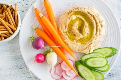 hummus on a white plate with low FODMAP vegetables and gluten-free pretzels