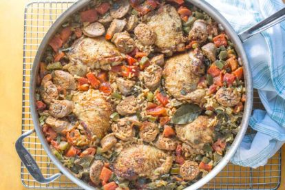 chicken and sausage jambalaya overhead in skillet with yellow background