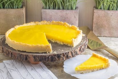 lemon curd tart on a wooden platter, a slice out on thew side on a white plate