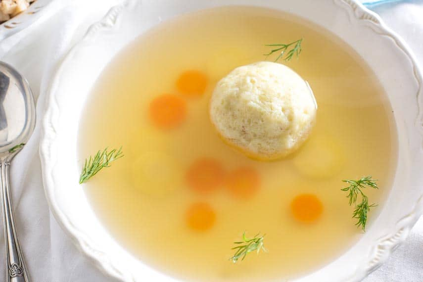 matzo ball soup in white bowl with fresh dill floating on top; silver spoon alongside