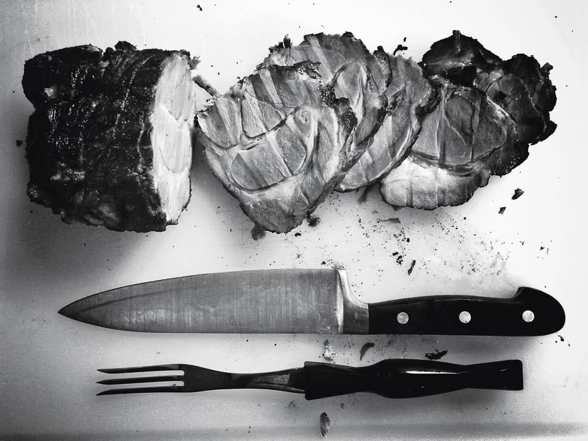 overhead black and white shot of sliced ham on a board with a carving knife and fork
