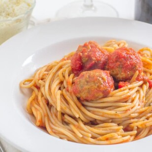 spaghetti & meatballs in a white bowl with Parmesan cheese in a small bowl in the background