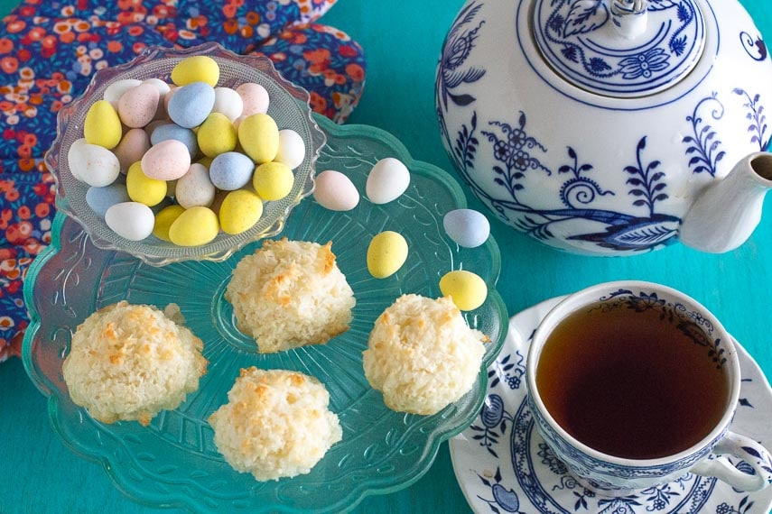 top view of coconut macaroons on green glass plate against aqua background; blue and white teapot in background