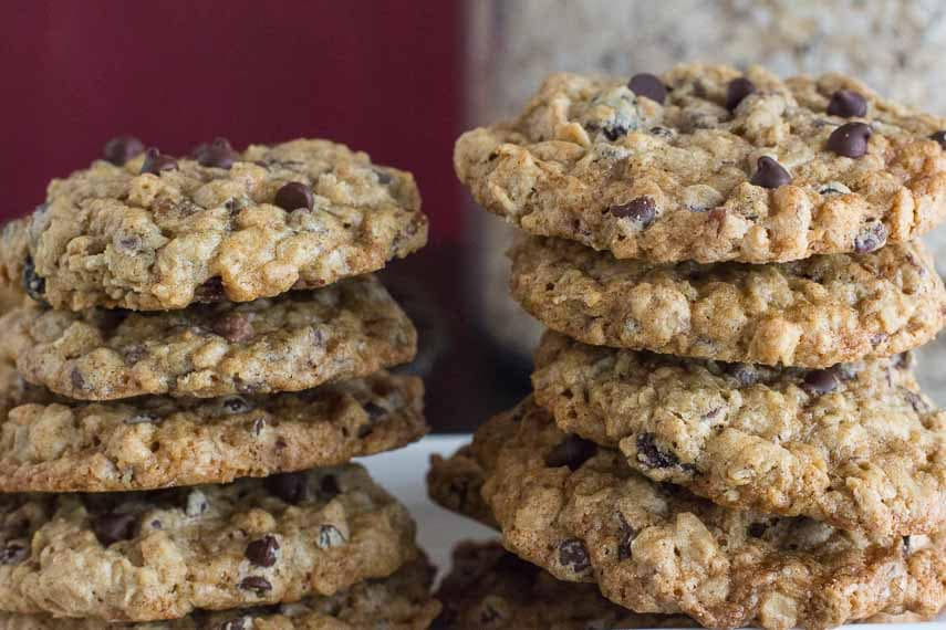 two stacks of oatmeal chcoolate chop cookies against a red background