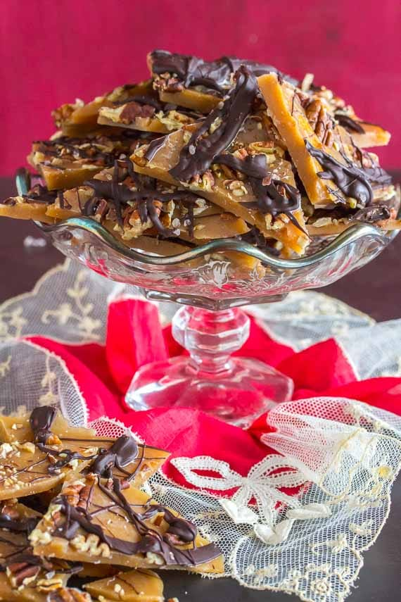 vertical image of pecan toffee image in footed glass dish with a red lace hankie