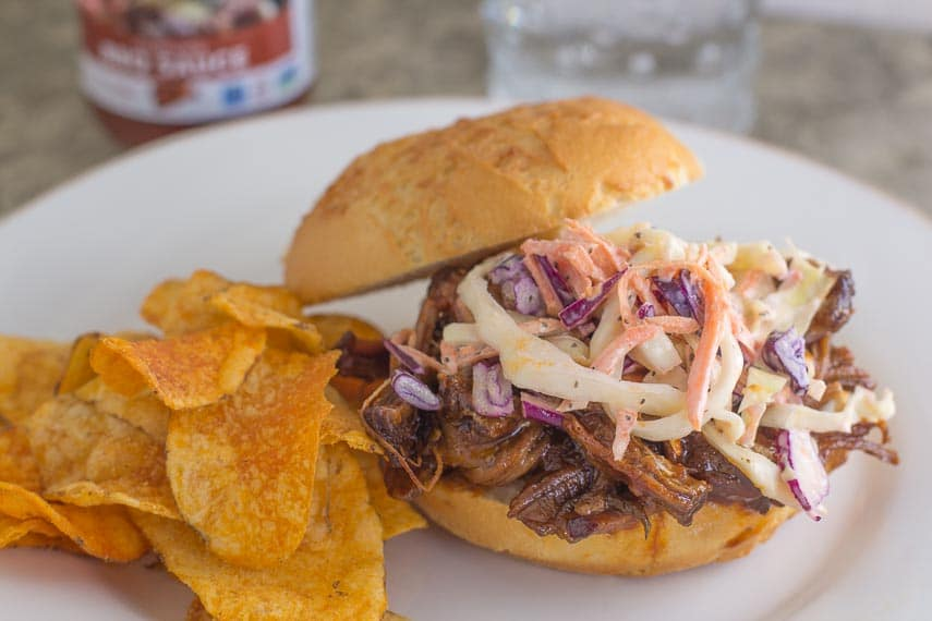 BBQ brisket topped with slaw on a roll with BBQ potato chips alongside