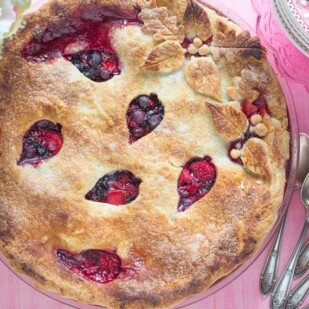 Overhead shot of berries pie, on a pink background, with decorative cut-outs in crust
