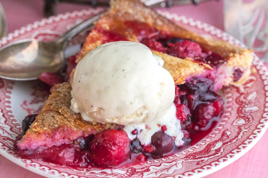berries pie, on a pink background, with decorative cut-outs in crust, with lactose-free ice cream