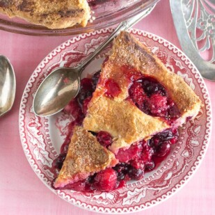 berries pie, on a pink background, with decorative cut-outs in crust