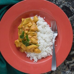 butter chicken with basmati rice in an orange bowl against a black quartz backdrop