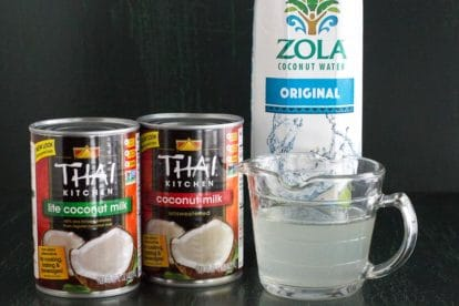 canned coconut milk and carton of coconut water against a dark background