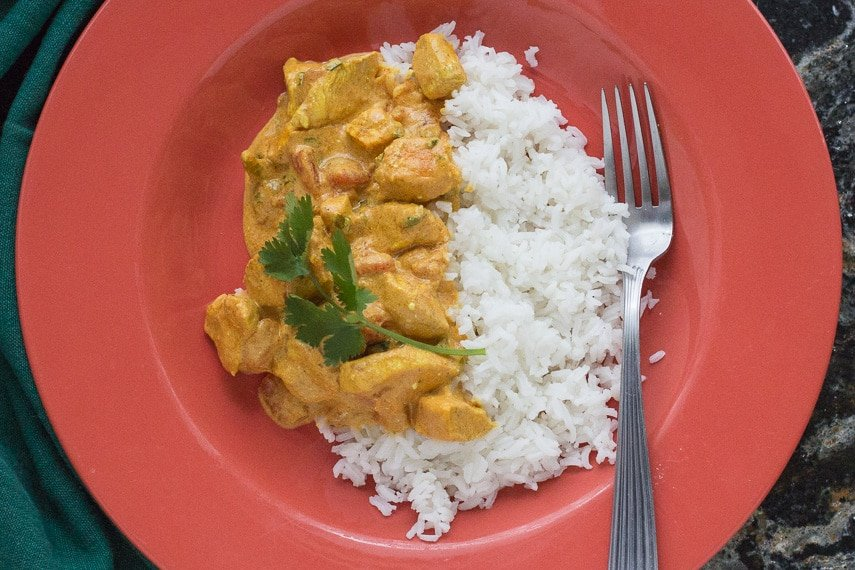 closeup of butter chicken and basmati rice in an orange bowl