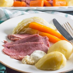 corned beef and cabbage and potatoes and carrots on a white plate