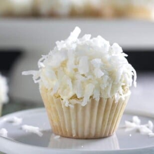 mini coconut cupcake, up close on a white plate