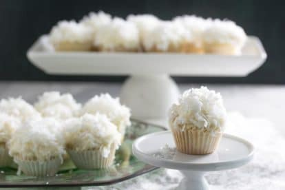 mini low FODMAP coconut cupcakes on a platter in the background, one in the foreground on a tiny white pedestal