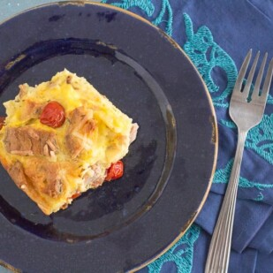 ham and egg strata on a blue plate with an embroidered blue napkin alongside